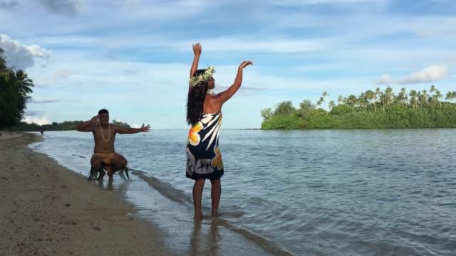Exotic Pacific Islander man and woman dancing at Muri lagoon in Rarotonga Cook Islands