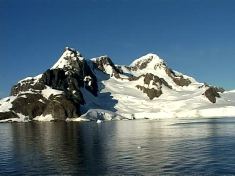 wa expanse of sea with mountain range horizon, pan left, sea water foreground, antarctic peninsula - antarctic peninsula stock videos & royalty-free footage