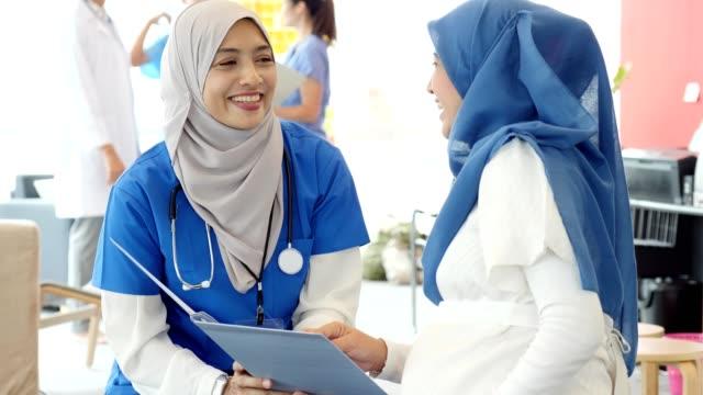 vídeos de stock, filmes e b-roll de a mãe expectante pede ob/gyn uma pergunta durante a nomeação médica - quadro médico