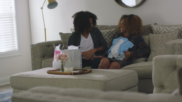 expecting african-american couple opening baby boy gifts at home on their sofa - baby clothing stock videos & royalty-free footage