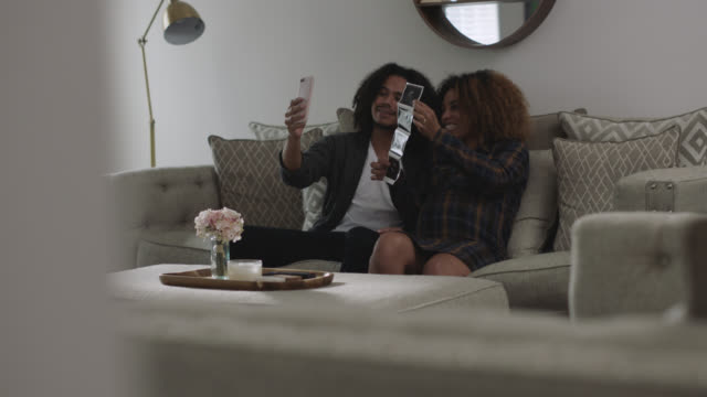stockvideo's en b-roll-footage met expecting african-american couple shares ultrasound photos over voice chat - aankondigingsbericht