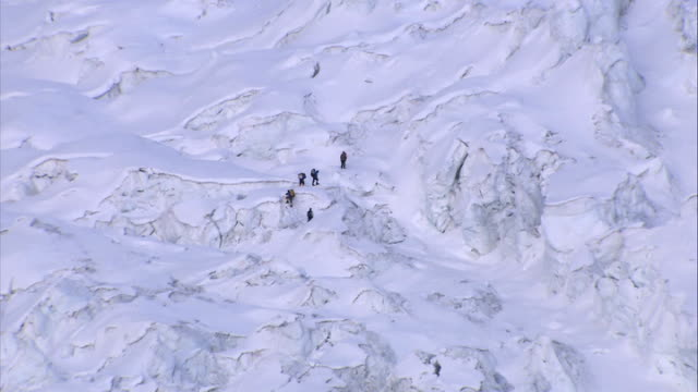 climbers on khumbu icefall more of climbers seen trekking in midst of vast icy terrain / general views of khumbu icefall showing seracs pan - khumbu stock videos and b-roll footage
