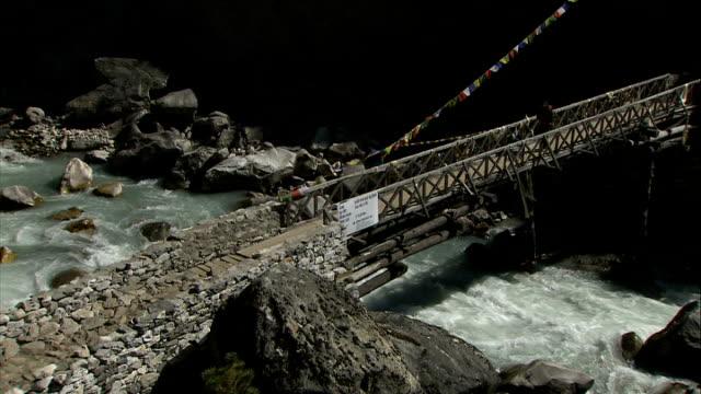 namche bazar and general views of himalayas damaged bridge and trekkers across suspension bridge river crossing / good shots of flowing mountain... - suspension bridge stock videos & royalty-free footage