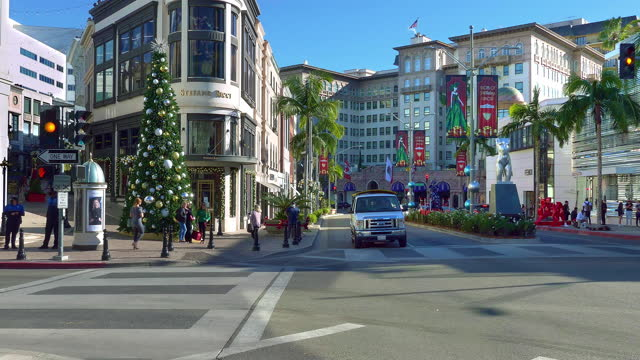 expensive luxury sport cars driving on rodeo drive in beverly hills at christmas, los angeles, california, 4k - the beverly hilton hotel stock videos & royalty-free footage