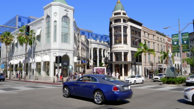 expensive luxury sport cars driving on rodeo drive in beverly hills, los angeles, california, 4k - ビバリーヒルズ点の映像素材/bロール