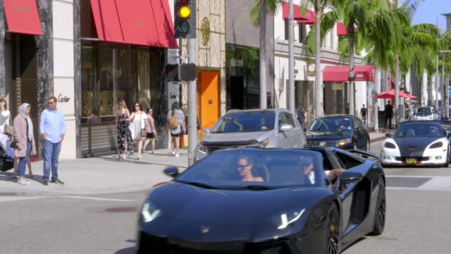 expensive luxury sport cars driving on rodeo drive in beverly hills, los angeles, california, 4k - beverly hills california stock videos & royalty-free footage