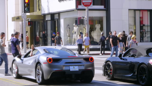 stockvideo's en b-roll-footage met expensive luxury sport cars driving on rodeo drive in beverly hills, los angeles, california, 4k - beverly hills californië