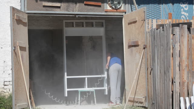 experienced carpenter in casual clothes with gas mask on and small buiness owner paints a wooden furniture in white color in workshop - airbrush stock videos & royalty-free footage
