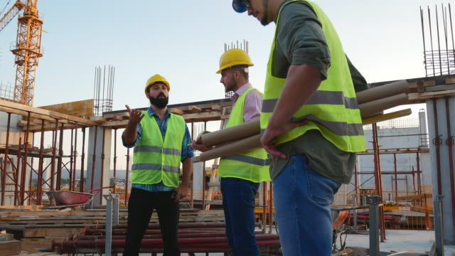 experienced engineers working on the construction site - operatore edile video stock e b–roll