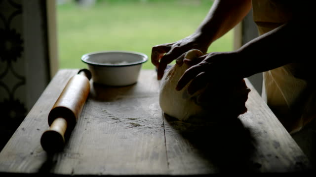 Erfahrene Hausfrau knetet den Teig auf dem Tisch in der Küche zu Hause.