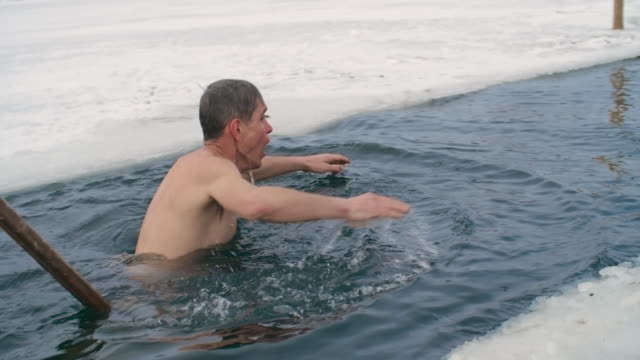 Experienced ice-swimmer practicing in frozen river