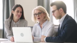 Experienced old female leader teaching mentoring business team with computer