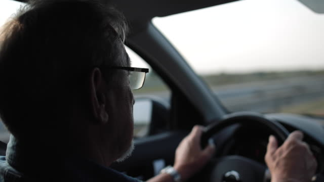 vídeos de stock e filmes b-roll de experienced older man with glasses drives a car - 65 69 anos