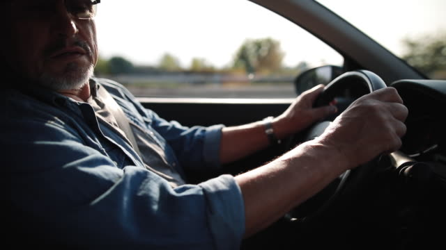 experienced older man with glasses drives a car - solo un uomo anziano video stock e b–roll