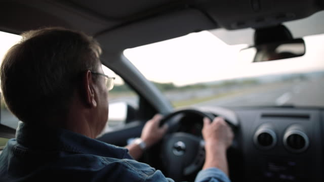 experienced older man with glasses drives a car - driving stock videos & royalty-free footage
