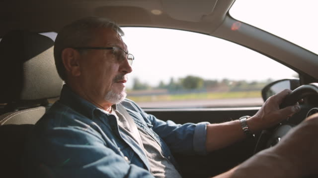 experienced older man with glasses drives a car - land vehicle stock videos & royalty-free footage