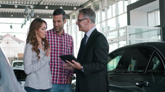 Experienced salesman selling a car to a young couple