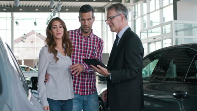 experienced salesman selling a car to a young couple - oggetto creato dall'uomo video stock e b–roll