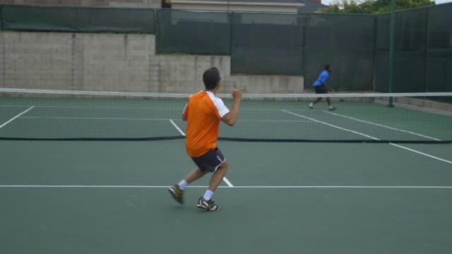 a experienced tennis player serving to a beginner tennis player. - slow motion - ziegenbart stock-videos und b-roll-filmmaterial