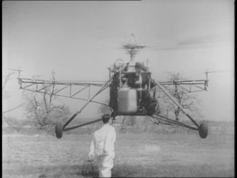 experimental model of a sikorsky helicopter lifts off 90 degrees from the ground near a tree / cameraman shoots footage of flight / helicopter sits... - kolibri stock-videos und b-roll-filmmaterial