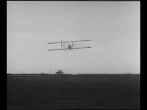 experimental pilot adjusts controls of early airplane / plane flies away / plane with propeller and boxlike wings / men guide plane in an attempt to... - 1910 stock-videos und b-roll-filmmaterial
