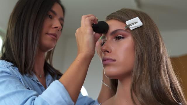 vídeos de stock, filmes e b-roll de maquiadora especialista colocando base no rosto de seu cliente - maquiagem