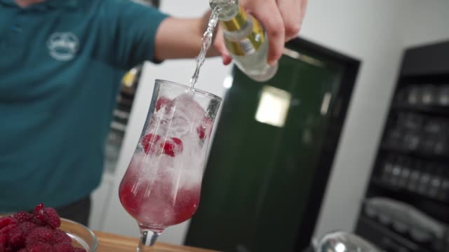 expertised bartender pouring sparkling juice to mix with alcohol and raspberries - b roll stock videos & royalty-free footage