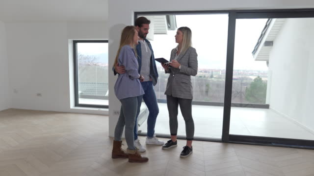 expertised female real estate agent showing unfurnished apartment for rent to a young married couple - three people stock videos & royalty-free footage