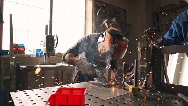 expertised industrial worker welding and metal frame in his metal workshop - welding helmet stock videos & royalty-free footage