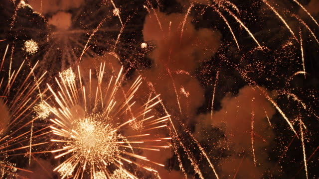 vídeos de stock e filmes b-roll de exploding fireworks and smoke fill the frame and the night sky in a violent grand finale. - aproximar imagem