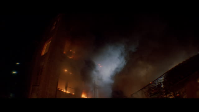 MS Exploding older brick warehouse style building and searchlights and scaffolding in front building / Unspecified