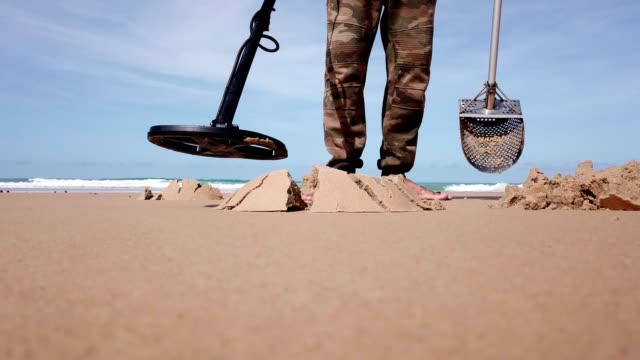 explore using metal detector on the sand beach - miner stock videos & royalty-free footage