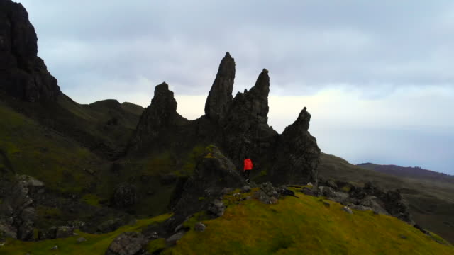 explorer on the top of the old man of storr in the mountains of the skye island. - hiking stock videos & royalty-free footage