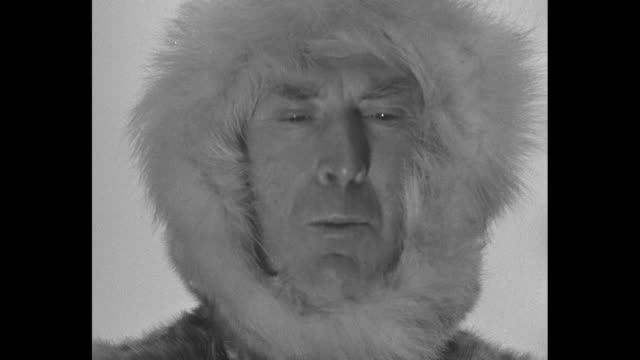 sot explorer robert bartlett his head framed by a fur hood talking to camera about arctic explorer robert peary / bartlett now wearing a beret and a... - effie stock videos and b-roll footage