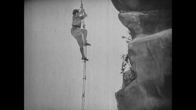 1925 Explorers climb down sheer cliff face using rope ladder