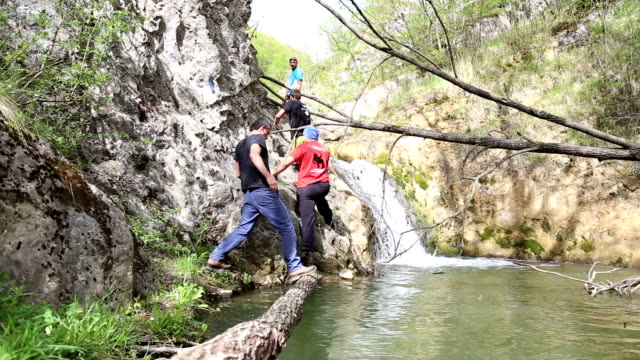 explorers crossing river on a log and climbing on rock - speleology stock videos and b-roll footage