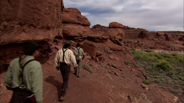 explorers hike along the edge of a valley. - historische szene stock-videos und b-roll-filmmaterial
