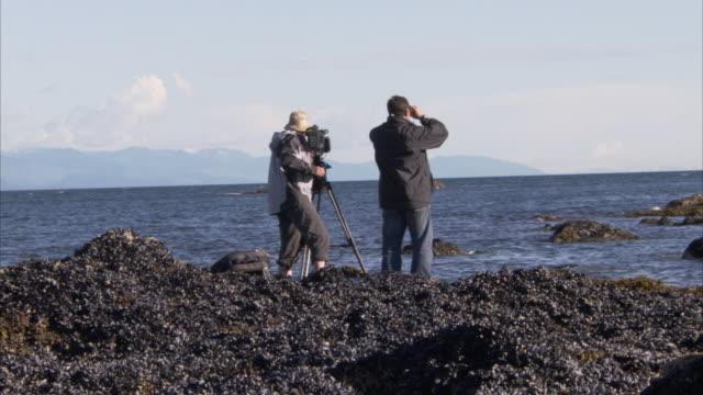 vídeos de stock e filmes b-roll de explorers view and film their surroundings. - explorador