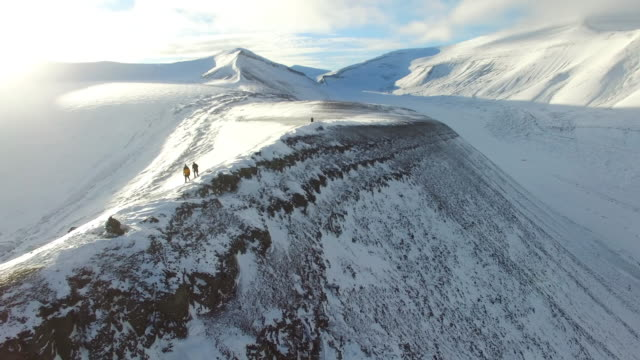 explorers walk atop mountain range, aerial circle view - norway stock videos & royalty-free footage