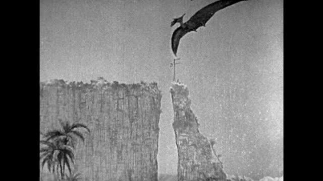 stockvideo's en b-roll-footage met 1925 explorers watch in awe as pterodactyl flies into view before landing on plateau edge to eat - 1925