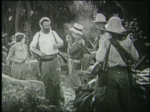 B/W explorers with guns talking in jungle, one man smokes pipe