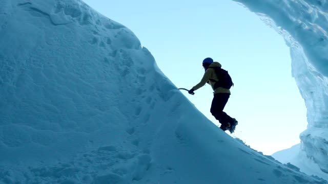 Exploring ice cave. Climbing on ice wall