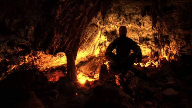 exploring mountain cave. meditating on a rock - geologist stock videos & royalty-free footage