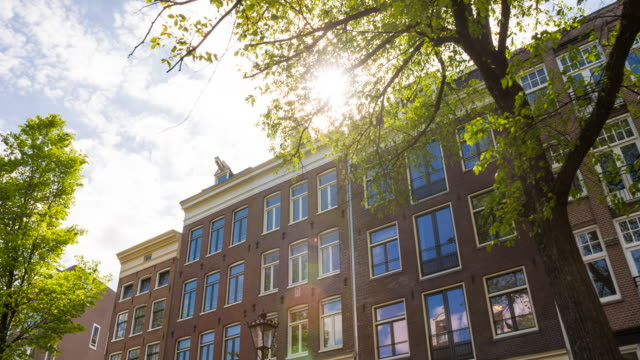 exploring the city of amsterdam, netherlands on a beautiful sunny day - townhouse stock videos & royalty-free footage