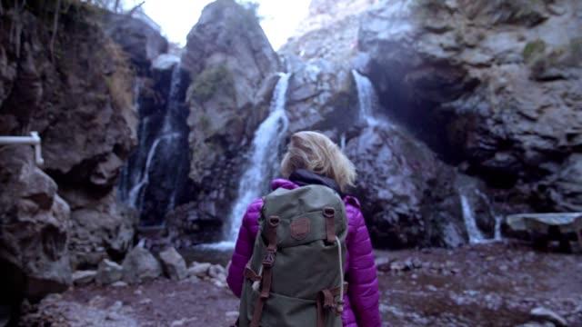 Exploring wilderness. Woman admiring mountain waterfall