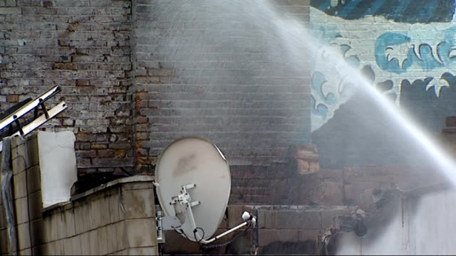 explosion and fire in workshop in camberwell england london camberwell ext wide shot water being hosed at workshop building with tape cordon in... - 非常線点の映像素材/bロール