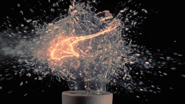 slo mo explosion of a light bulb - 壊れた点の映像素材/bロール