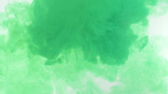 explosion of bright green ink on a white background - curlicue stock videos & royalty-free footage