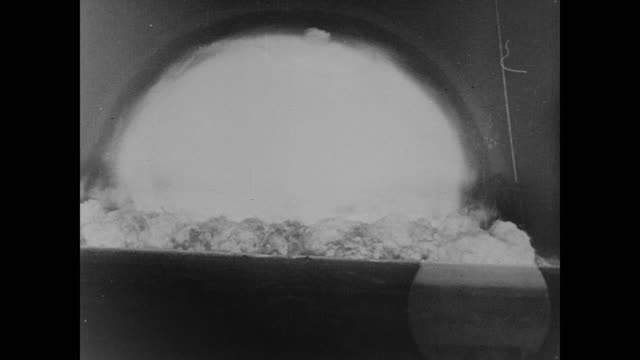 explosion of the atomic bomb and a tally of its devastation - 1945 stock-videos und b-roll-filmmaterial
