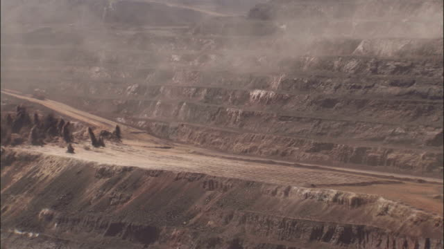 explosions across a strip-mining operation create billows of smoke. available in hd. - open cast mine stock videos & royalty-free footage